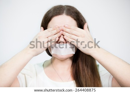 Caucasian woman covering her eyes with hands while mouth sealed with tape - stock photo