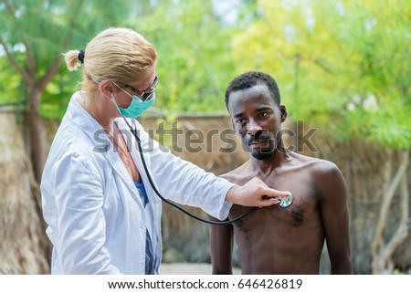 Caucasian woman doctor listening the hearth beat and breathing of sick black African man