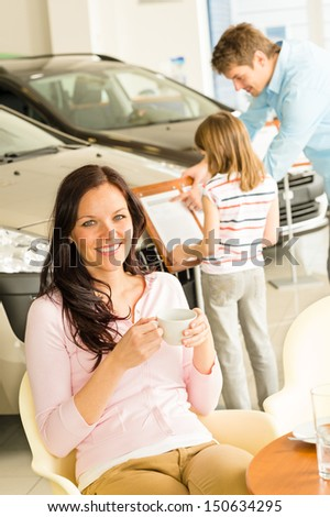Caucasian woman drinking coffee in car retail store - stock photo