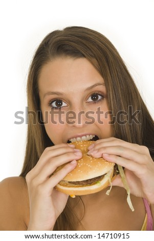 Caucasian woman eating a hambuger on a white background