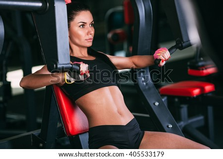 caucasian woman exercising on shoulder press machine