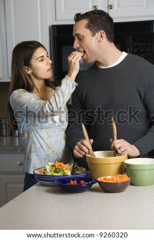 Caucasian woman feeding man at kitchen counter while he makes salad. - stock photo