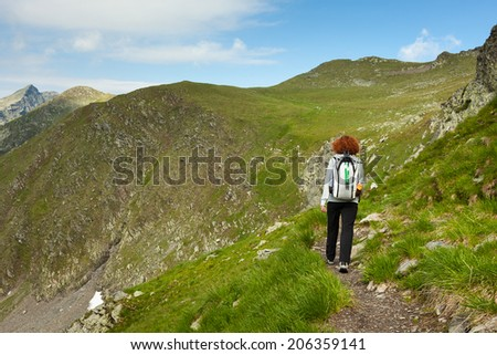 Caucasian woman hiking alone in the Fagaras mountains in Romania - stock photo