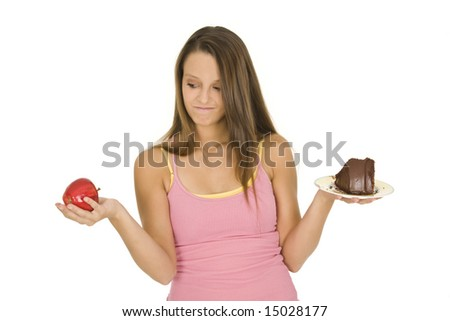Caucasian woman holding an apple and slice of chocolate cake trying to decide which one to eat