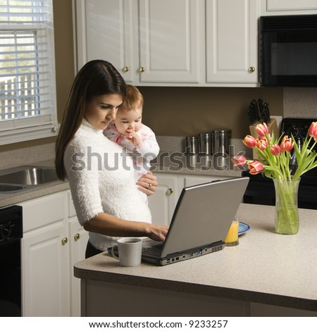 Caucasian woman holding baby  and typing on laptop computer in kitchen. - stock photo