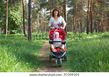 caucasian woman holding carriage with her little son in summer park background - stock photo