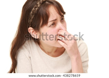 caucasian woman holding her nose because of a bad smell - stock photo
