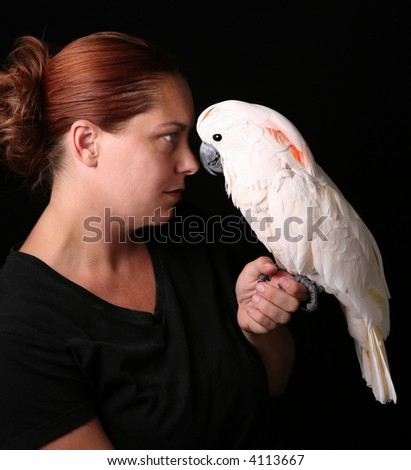 Caucasian Woman Holding Her Pet Moluccan Cockatoo on Black