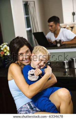 Caucasian woman hugging toddler son in kitchen with father on laptop in background. - stock photo