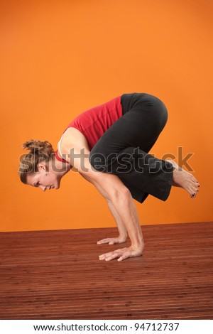 Caucasian woman in Bakasana crane pose over orange background - stock photo