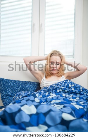 caucasian woman in bed, getting up late to work with terrible hangover, funny concept - stock photo