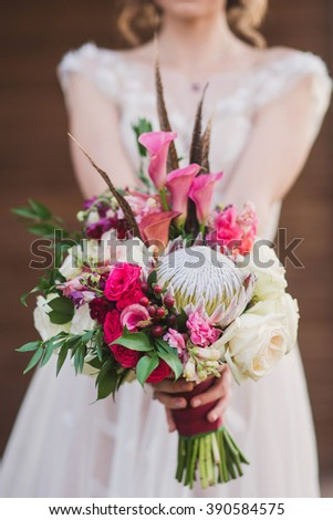 caucasian woman in beige wedding dress hold a bouquet of roses, berries and leaves with protea flower - stock photo
