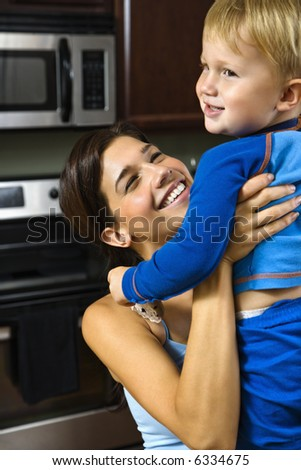Caucasian woman in kitchen lifting smiling toddler son into the air. - stock photo