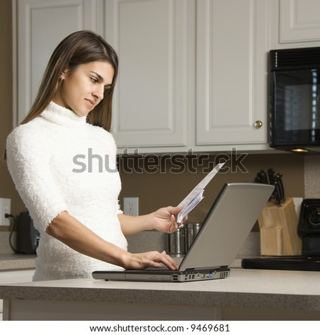 Caucasian woman in kitchen looking at laptop computer. - stock photo