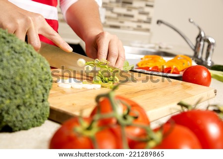 caucasian woman is cutting raw vegetables  on the kitchen table