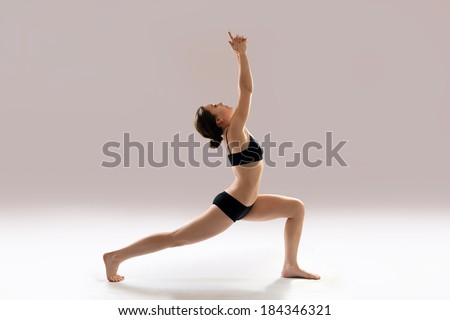 Caucasian woman is practicing yoga . In studio.  grey background. - stock photo