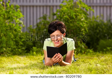 caucasian woman is reading the e-book lying on the grass in the park - stock photo