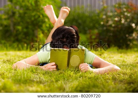 caucasian woman is reading the green book lying on the grass in the park - stock photo