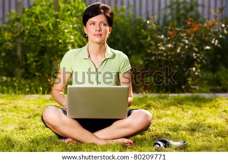 caucasian woman is sitting on the grass with laptop