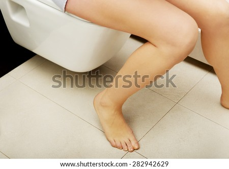 Caucasian woman is sitting on the toilet. - stock photo
