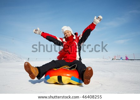 caucasian woman is sliding fast downhill on an inner tube