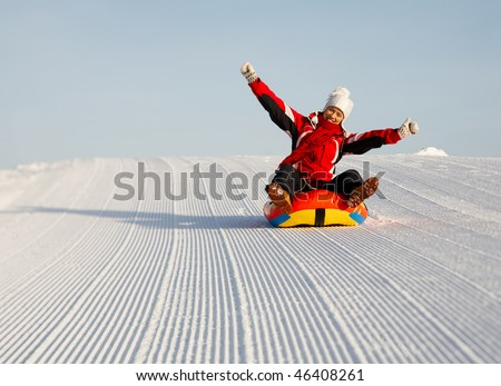 caucasian woman is sliding fast downhill on an inner tube - stock photo