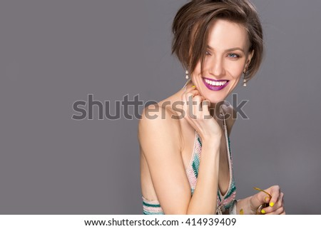 Caucasian woman isolated on grey background. Casual woman with short hairstyle and summer outfit smiling looking happy  - stock photo