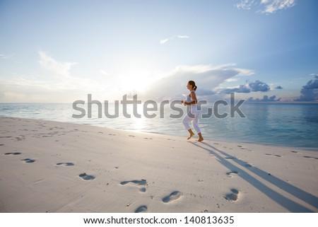 Caucasian woman jogging at seashore - stock photo
