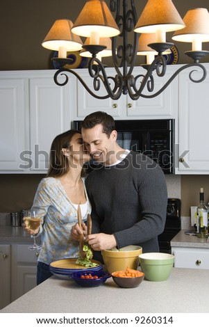 Caucasian woman kissing man at kitchen counter. - stock photo