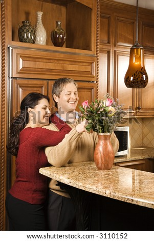 Caucasian woman leaning on Caucasian man while he arranges flowers in vase in kitchen. - stock photo