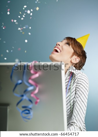 caucasian woman looking at confetti being thrown in office. Vertical shape, side view, waist up, copy space