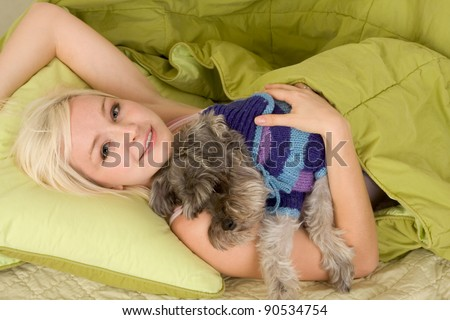 Caucasian woman lying down on bed and holding dog of Schnauzer breed