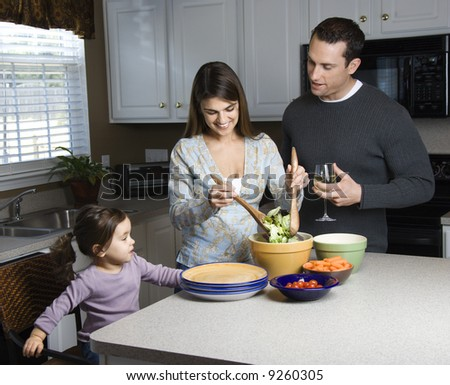 Caucasian woman making salad on kitchen counter with daughter and husband. - stock photo