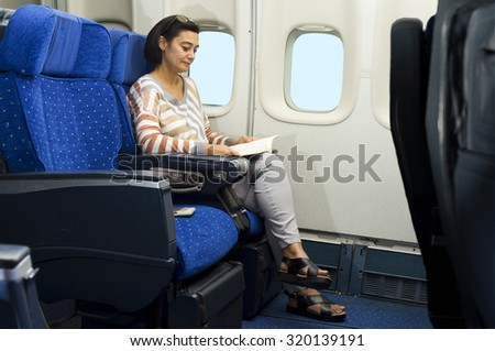 caucasian woman passenger in airplane reading a book on the seat  in comfortable flight and trip - stock photo