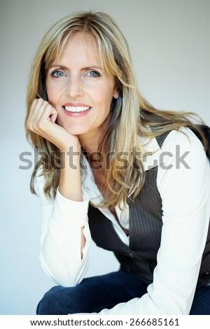 Caucasian woman posing in studio in semi-formal attire. - stock photo