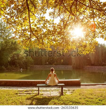 Caucasian woman practicing yoga at lake - stock photo