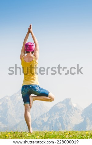 Caucasian woman practicing yoga high in the mountains - stock photo