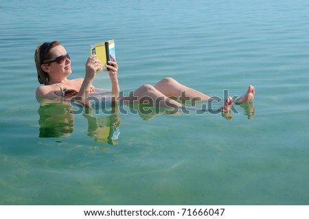 Caucasian woman reads a book floating in the waters of the Dead Sea in Israel - stock photo