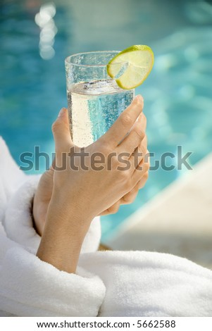 Caucasian woman's hands holding beverage glass garnished with lime slice next to pool.