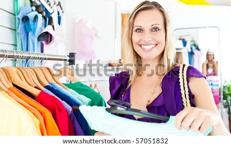 Caucasian woman selecting item in a clothes shop - stock photo
