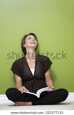 caucasian woman sitting in the green room reading a book - stock photo