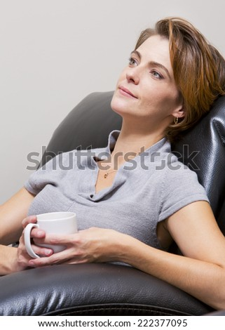 caucasian woman sitting in the living room drinking coffee