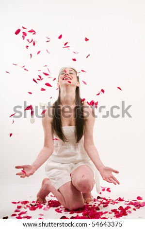 Caucasian woman throw petals of red roses