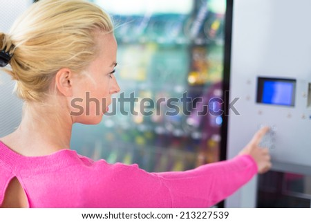 Caucasian woman using a vending machine that dispenses snacks. She is looking on the blue display screen of machine. - stock photo
