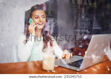 Caucasian woman using laptop and mobile phone behind the glass of a cafe - stock photo