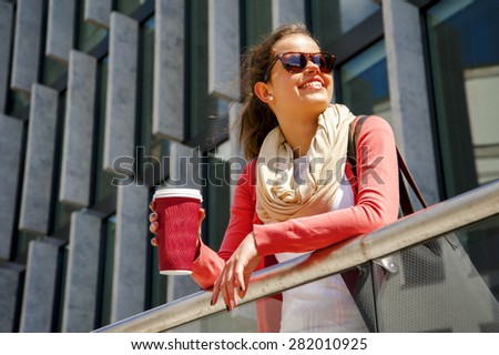 Caucasian woman Vivacious in City with a beautiful beaming smile backlit by the warm glow of the sun shining down City. - stock photo