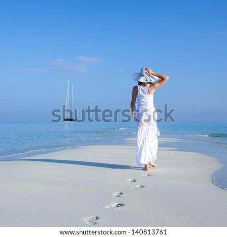 Caucasian woman walks along beautiful seashore - stock photo