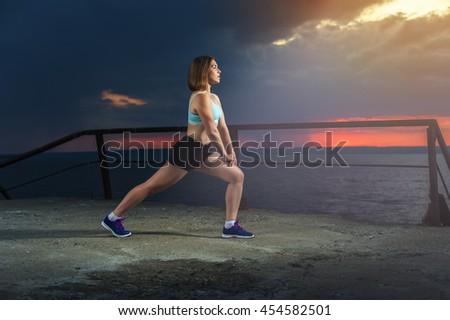 Caucasian woman warming up on the sea pier. Fitness workout outdoors - stock photo