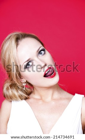 Caucasian woman wearing white dress on red background licking her lips - stock photo