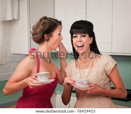Caucasian woman whispers joke to friend in her kitchen - stock photo
